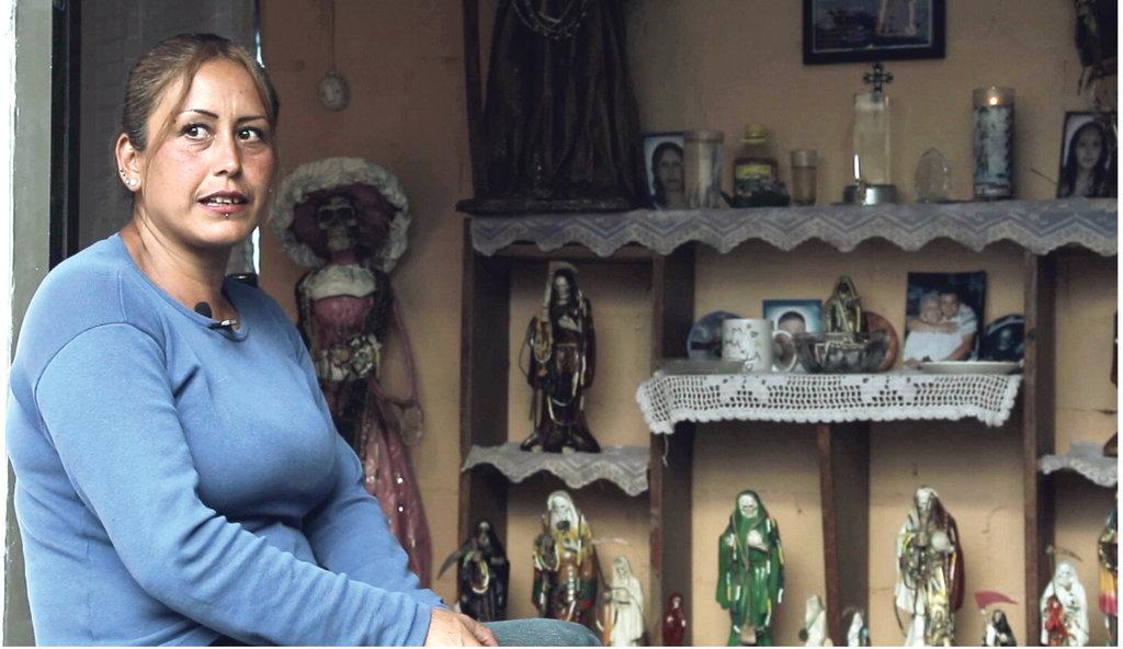 Dulce Galván, resguardada por las efigies del altar a la Santa Muerte.