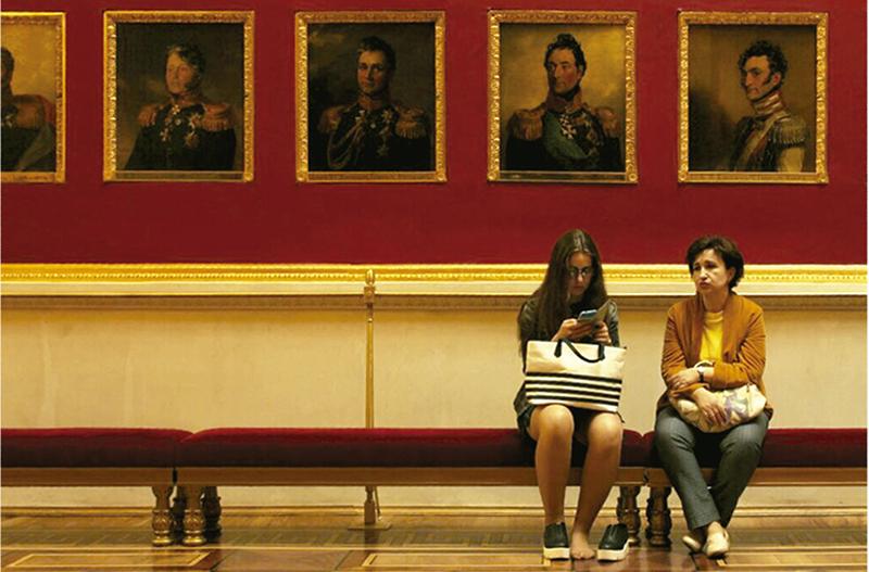 Dos mujeres descansan sobre una banca en el célebre Pasillo de los Retratos