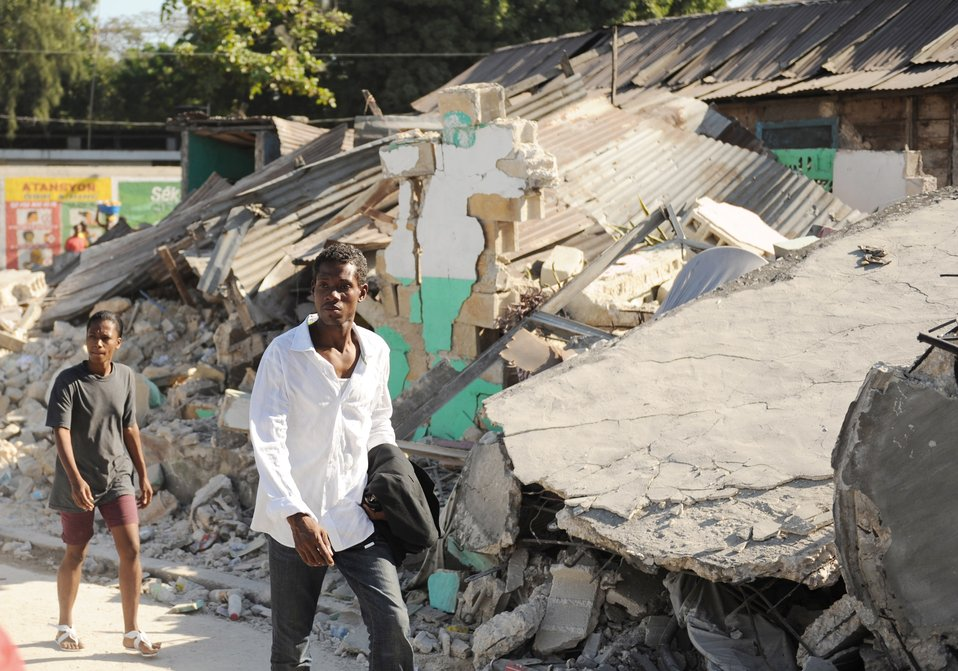 Haitianos caminan junto a escombros. 17 de enero del 2010, en Port-au-Prince, Haití después de un terremoto de magnitud 7 que azotó la ciudad el 12 de enero de 2010.  Fotografía por James L. Harper Jr.