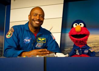 El astronauta Leland Melvin en conversación con Elmo. Nasa.